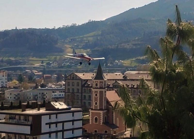 Ultraleichtflugzeug tief über Brixen
